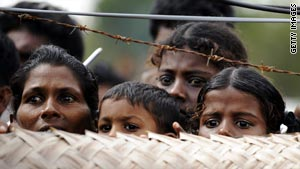 Sri Lankan war-displaced civilians peer from behind barbed wire fences surrounding their internment camp in Vavuniya