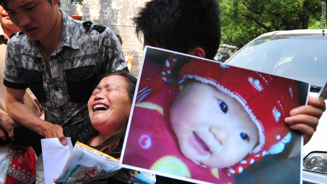 Zheng Shuzhen holds a portrait of her grand-daughter in Beijing on May 8, 2009. She claims the child's death from tainted milk was never dealt with appropriately by their local government.
