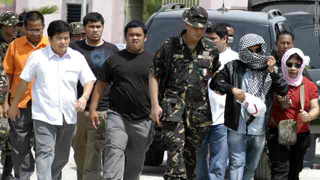 Andal Ampatuan, 2nd from right, accompanied by his wife and brother, Mindanao Governor Zaldy Ampatuan, left in white, surrenders Thursday in Maguindanao.