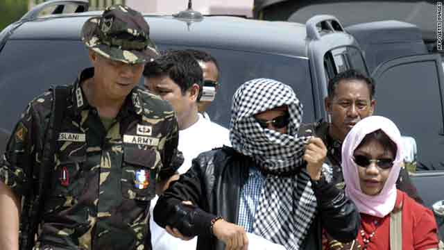 Andal Ampatuan Jr., center, with his wife is escorted by military personnel in Maguindanao on Thursday.