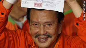 Joseph Estrada shows off his presidential candidacy certificate at the electoral commission on November 30, 2009.