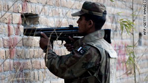 A Pakistani soldier aims his weapon through holes in a wall outside a besieged mosque in Rawalpindi.