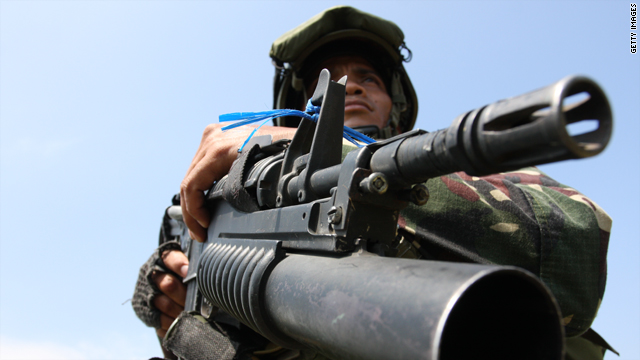 A Filipino soldier secures the site where weapons and ammunition were dug up on December 6 in Maguindanao.