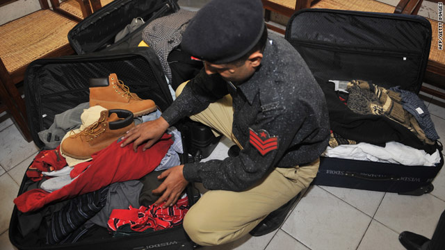 A Pakistani police officer Monday searches a Karachi hotel room  where the five detained Americans reportedly had stayed.