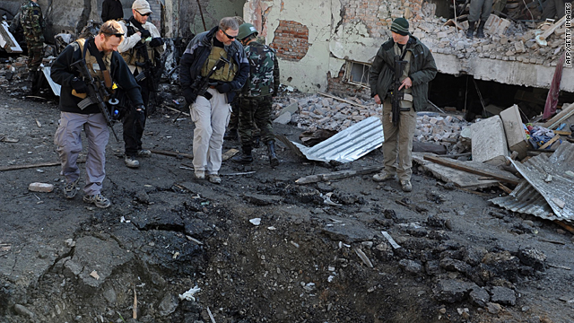 Foreign investigators inspect a crater left by the blast on Tuesday December 15 in Kabul.