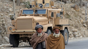 Two Afghan men pass U.S. troops in Nuristan Province, Afghanistan, on Sunday.
