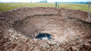 Officials check out a crater Monday near Mazsalaca, Latvia.