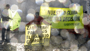 "Greenpeace protesters stage an ""extreme weather"" event at the climate conference center in Barcelona."