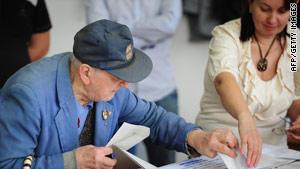 An election worker helps an elderly man cast his vote in Bucharest.