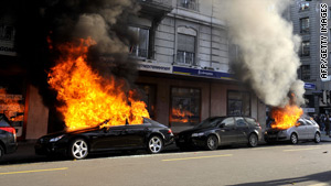 Torched cars burn in a street in Geneva after anti-WTO demonstrations turned violent on Saturday.