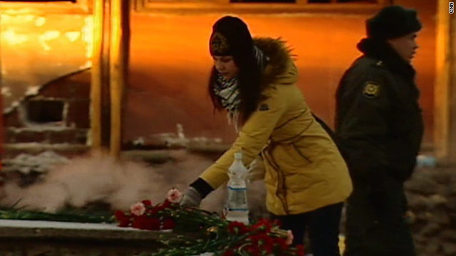 A woman lays flowers at the scene of the Russian nightclub fire where 109 people were killed.