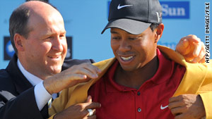 Tiger Woods dons the winner's jacket at the close of the Australian Masters in November.