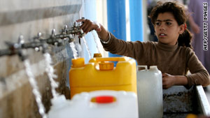A girl fills water bottles at a United Nations relief camp in Gaza on Tuesday.