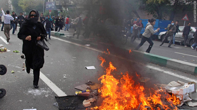 Anti-government protesters run from riot police in Tehran, Iran, on Wednesday.