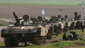 Israeli troops and armored vehicles wait on the Israel-Gaza border in January.