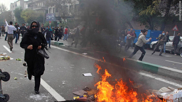 Demonstrators run from riot police Wednesday in Tehran, Iran. More than 100 were arrested.