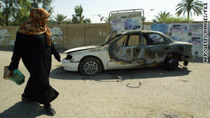 A woman walks past a burned-out car after the 2007 incident in which Blackwater security personnel killed 17 people.