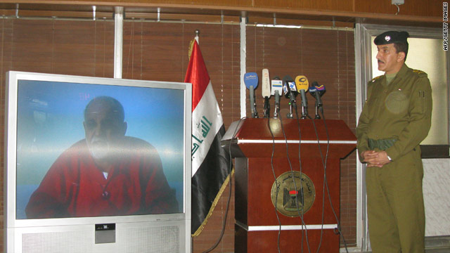 Iraqi Maj. Gen. Qassem Atta watches a video showing an alleged confession, aired in Baghdad, Iraq, on Sunday.