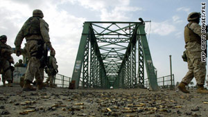 U.S. soldiers in 2004 walk on the bridge where the burned bodies of American contractors were hung.