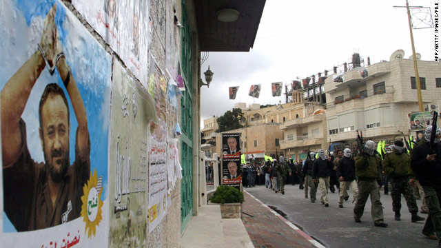 Palestinian militants march past a wall poster of Marwan Barghouti in 2006.
