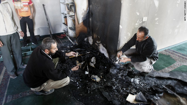 Palestinians inspect damage to a mosque that was set on fire in the West Bank village of Yasuf.