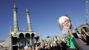 Iranians hold portraits of Grand Ayatollah Hossein Ali Montazeri at  his funeral procession in Qom on Monday.