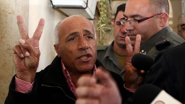 "Mordechai Vanunu flashes the ""V"" sign as he is brought into an Israeli court Tuesday in Jerusalem."