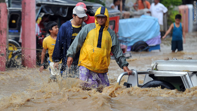 Residents of a town south of Manila wade through a flooded street caused by Typhoon Mirinae on Saturday