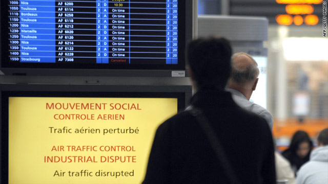 A passenger stands in front of a screen announcing an air traffic control dispute at Paris Orly airport.