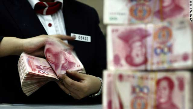 A bank worker arranges stacks of 100-yuan notes in Suining in southwest China's Sichuan province on Saturday.
