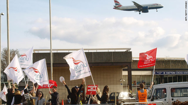 A BA plane approaches Heathrow Airport in London in front of a Unite union picket.