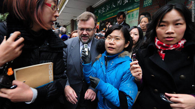 Australian Consul-General Tom Connor is surrounded by journalists outside the court in Shanghai as the trial ended.