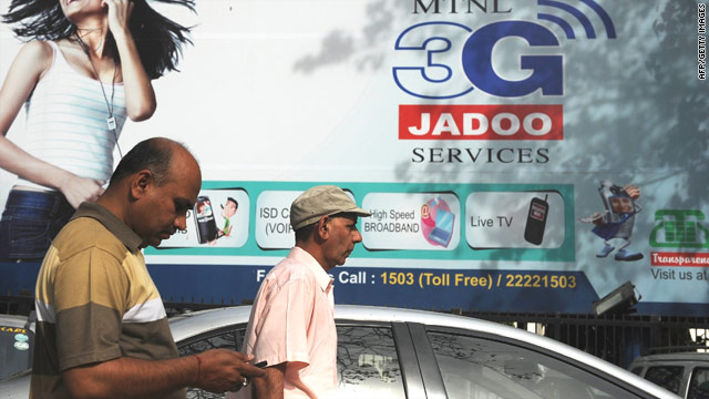 Men walk past an advertisement for 3G telecom services in New  Delhi on April 9, 2010.