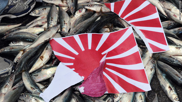 A torn apart Japanese 'Rising Sun' flag is placed on dead fish during a demonstration in front of the Japan Exchange Association - Japan's representative office on Taiwan- on September 14 over the continued island dispute between Tokyo and Beijing.