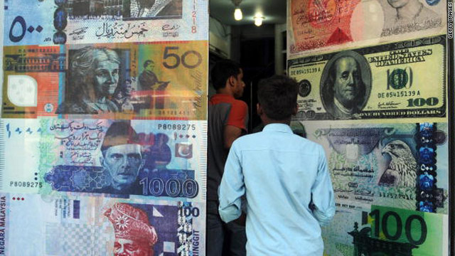 Pakistani customers enter a foreign currency exchange shop in Karachi, Pakistan, on October 14, 2010.