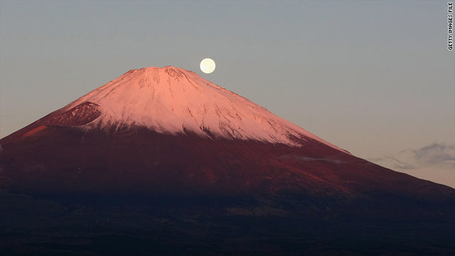 The sun sets as the moon rises on Japan's iconic Mount Fuji.