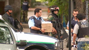 A policeman carries pizza that robbers ordered during the January 2006 bank heist in Acassuso, Argentina.