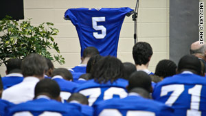 Rajaan Bennett's teammates gather in front of his football jersey at a memorial service Wednesday evening.