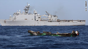 The burned hull of a suspected pirate skiff drifts near the USS Ashland after an attack on the Ashland on April 10.