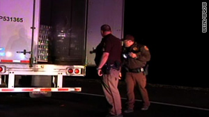 Officers inspect the truck, which was operated by a driver from Canada who does not speak English.