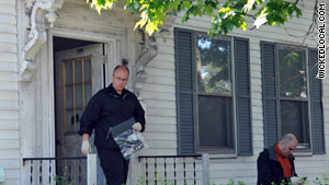 An investigator carries a plastic bag from a house in Watertown, Massachusetts, on Thursday.