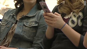A school district is being sued after a woman claims officials saw semi-nude photos on her cell phone and notified police.