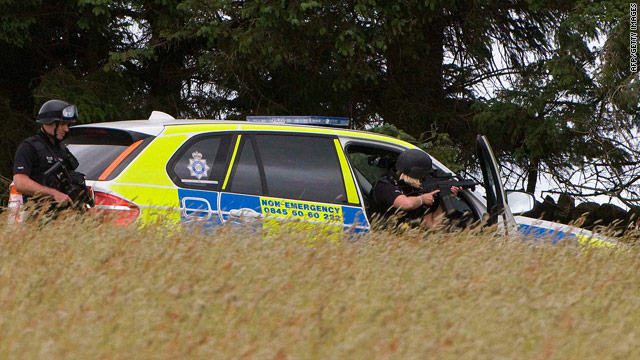 Police search farmland about 15 miles north of Rothbury, England, on Thursday for murder suspect Raoul T. Moat.