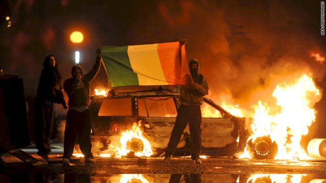 Men hold the Irish flag in front of burning cars during Nationalist rioting in the Ardoyne area of North Belfast on July 12, 2010.