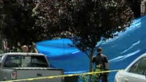 Police kept the scene covered as the bodies of the victims were brought out on Thursday.