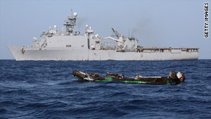 The burned out hull of a suspected pirate skiff drifts near the USS Ashland on April 10, 2010, in the Gulf of Aden.