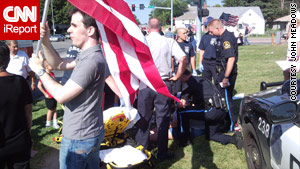Police talk to witnesses after a motorist pepper sprayed a small group of people near a funeral for a Marine.
