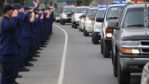 Coast Guardsmen salute a procession of police cars carrying the urns of two slain police officers Wednesday.