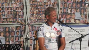 Ed Smart, whose daughter was kidnapped, addresses the crowd. Behind him are photos of victimized children.