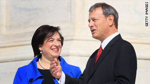 Justice Elena Kagan, here with Chief Justice John Roberts, served her first day on the Supreme Court on Monday.
